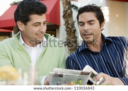 Men together reading newspaper at cafe