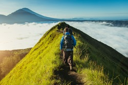 Men walk along the hill with backpacks and with white clouds and peak of volcano on background