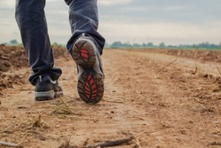 Men wear jeans and wear walking shoes on the dirt road.shoes closeup
