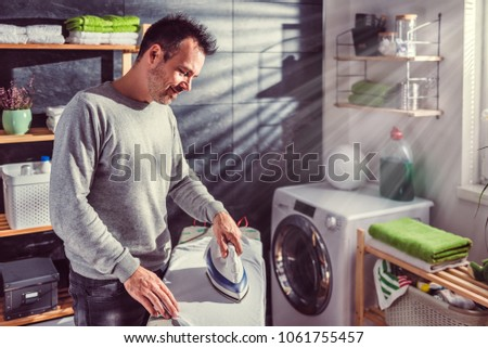 Men wearing grey sweater ironing clothes on ironing board in laundry room at home #1061755457