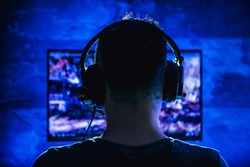Men wearing headphones playing video games late at night