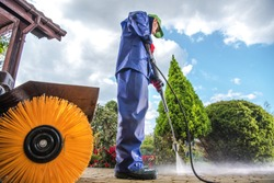 Men Wearing Industrial Wet Coat Cleaning Residential Driveway using Power Pressure Washer.