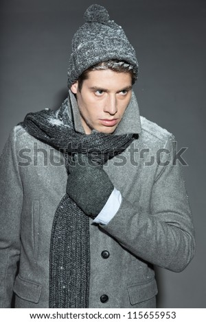 Men winter fashion. Handsome man with brown hair wearing grey scarf, grey woolen hat, grey woolen gloves and grey coat. Covered with snow. Cold. Casual look. Studio shot isolated on grey background.