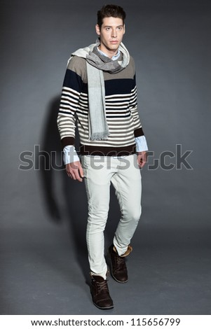 Men winter fashion. Handsome man with brown hair wearing grey scarf, striped sweater and white pants. Casual look. Studio shot isolated on grey background.