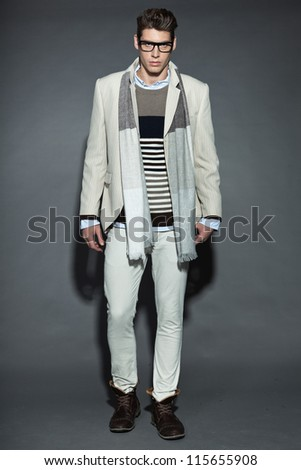 Men winter fashion. Handsome man with brown hair wearing grey scarf, striped sweater, white striped jacket, white pants and black glasses. Casual look. Studio shot isolated on grey background.