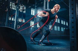 Men with battle rope battle ropes exercise in the fitness gym. CrossFit concept.