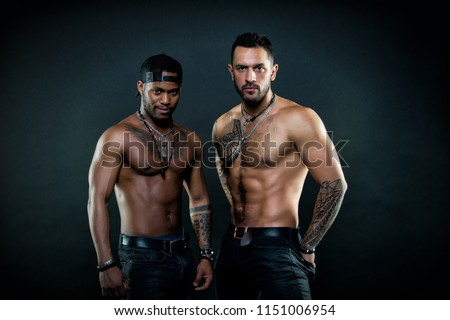 Men with fit sexy bodies. African man with charming smile wearing baseball cap. Sportsmen with tattooed chests and arms isolated on black background, body care concept. Athletes preparing for contest.