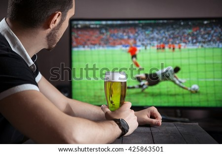 Men with glass of beer watch soccer match in bar.