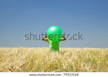 Men with green ball at wheat field.