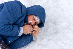 Men with hypothermia lying down surrounded by frozen winter landscape. Photo of a young man curled up on a frozen forest, trying to keep himself worm. Man snow covered, lying on the ground in snowfall