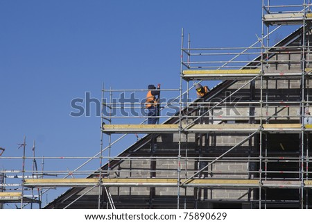 Men working at the new construction site with blue sky on background.