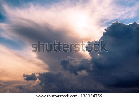 Menacing sky with clouds and sun emerging through translucent clouds