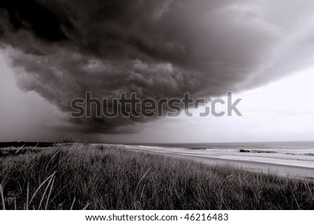 Menacing thunderstorm with dark clouds over sand dunes and beach at the New Jersey Shore