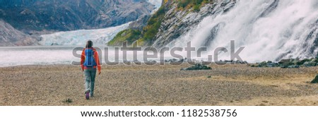 Mendenhall glacier in Juneau, Alaska. Woman tourist hiking with backpack in landscape background, panoramic banner header crop.