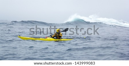 MENDOCINO, CALIFORNIA, USA - JUNE 8. Kayaker paddle open coast of Pacific Ocean in Mendocino county on June 8, 2013. Kayaking in big waves of open ocean coast is a discipline of extreme sea kayaking.