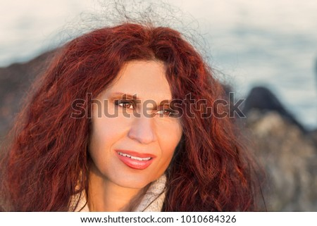 menopausal woman with red hair smiling, Caucasian but with Amerindian and Middle Eastern traits on background of sea and rocks