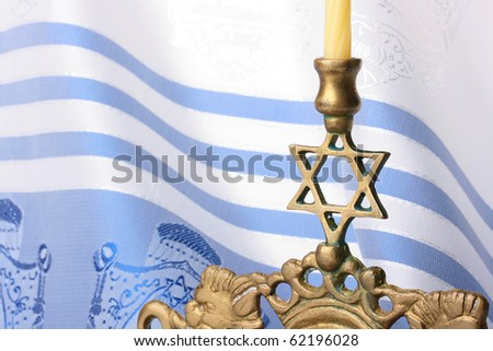 Menorah standing in front of a blue and white tallit. Add your text to the background.