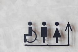 mens and womens disabled restroom signage with arrow made from steel plate on grey concrete wall.