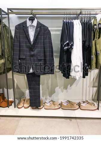 Mens fashion r suits in different colors shirt with pants hanging on hanger in a retail clothes store   Stock fotó ©