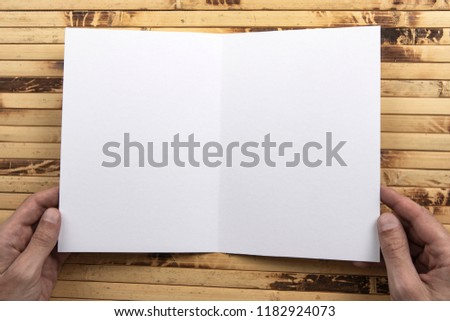 Mens hands holding empty white booklet on bamboo background. View from above #1182924073