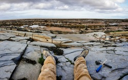 Mens legs and boots outstretched with mallet and chisel placed to the side on a British slate coast during low tide with ammonite fossils in the rock