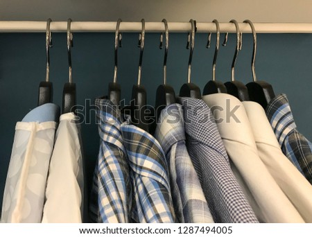 Mens Shirts. Blue and White Color Clothes. Male Clothes on Open Clothes Rail