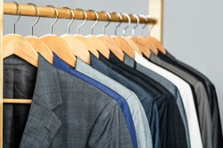 Mens suits in different colors hanging on hanger in a retail clothes store, close-up. Mens shirts, suit hanging on rack. Hangers with jackets on them in boutique. Suits for men hanging on the rack.