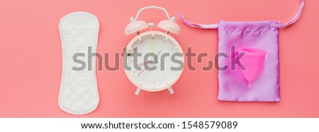 Menstrual cup with bag, hygienic pad, alarm clock on pink background. Alternative feminine hygiene product during the period. Women health concept.  #1548579089