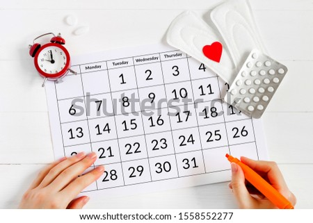 Menstruation calendar with pads, alarm clock, hormonal contraceptive pills. Female's menstrual cycle concept. Pain reliever for menstrual pain