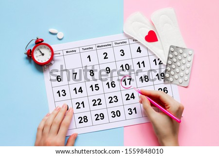 Menstruation calendar with pads, alarm clock, hormonal contraceptive pills. Female's menstrual cycle concept. Menstrual retardation concept