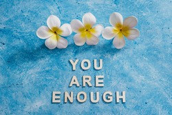 mental health and self-worth concept, You are enouugh text with flowers and blue background