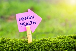 mental health arrow sign on green moss with sunshine background