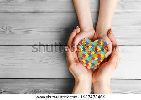 mental health care concept with puzzle or jigsaw pattern on heart Female hands hold childrens palms with a red heart in them. The concept of family love and support. World Autism Awareness day