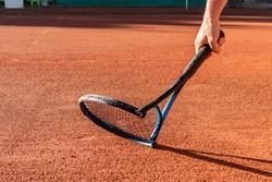 Mental health in sports. Frustrated tennis player broke his racket in fit of anger. Broken tennis racket on clay tennis court. Negative emotions, stress, dissatisfaction, defeat, crash, failure, loss