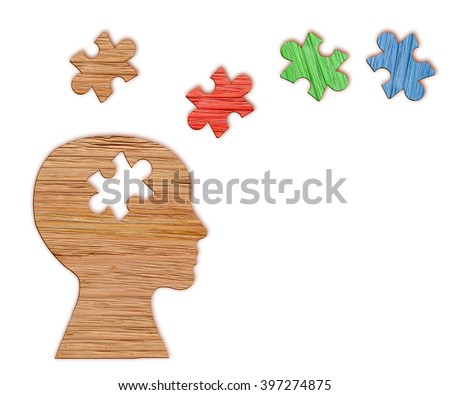 Mental health symbol. Human head silhouette with a puzzle cut out from wooden background