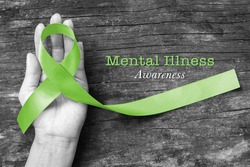 Mental illness awareness text with Lime Green ribbon color on helping hand on old aged wood background (clipping path)