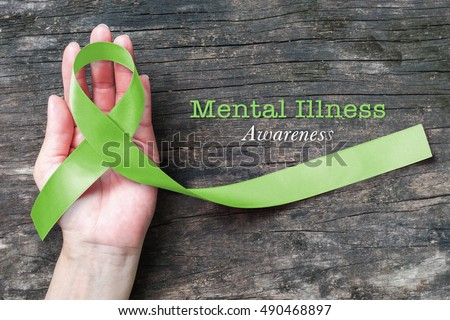 Mental illness awareness with Lime Green ribbon color  on helping hand #490468897