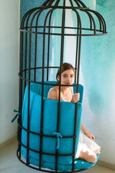 mental mind. prisoner woman in cage - home confinement. freedom of cute girl in cage chair. fashion slave in captivity of beauty. modern furniture design and home comfort. pretty woman in iron cage.