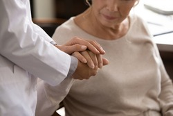 Mental support. Close up of disabled sick senior female hand in palms of young woman in white medical uniform. Attending physician nurse comforting taking care of unhealthy aged lady geriatric patient