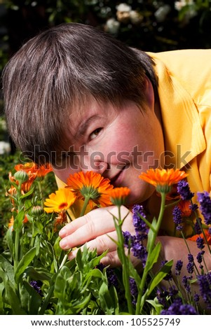 mentally disabled woman is in the garden and smell on flowers