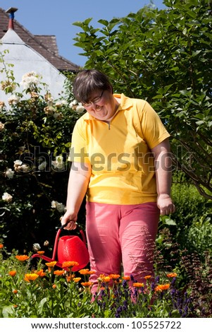 mentally disabled woman stands in the garden and  poured  flowers