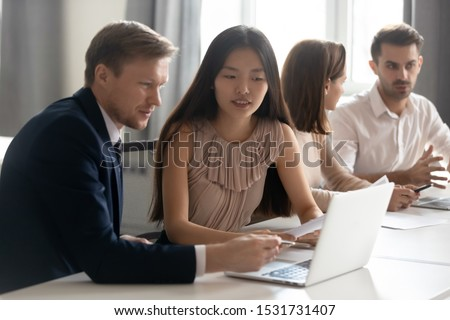 Mentor coach helping Asian female employee with corporate software, diverse colleagues working on project together at group meeting, discussing statistics, using laptop, manager consulting client