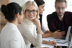 Mentor explaining project task to intern. Female professionals talking at workplace. New employee consulting friendly colleague. Workers discussing office news. Cooperation, mentorship concept