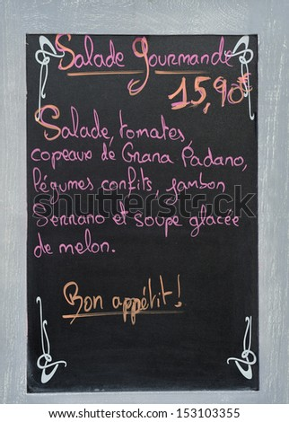 Menu board with advertisement for a salade gourmande at a French restaurant