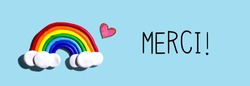 Merci - Thank you in french language with a rainbow and a heart