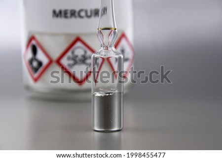 Mercury chemical element stock images. Laboratory accessories images. Mercury in a sealed ampoule stock photo. Laboratory equipment on a silver background. Hg, toxic chemical element stock images