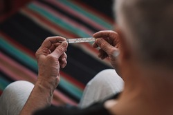 mercury thermometer in the hands of an elderly man. health care concept, prevention of colds.