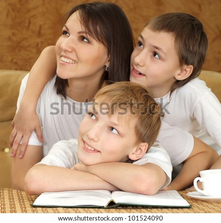 Mercy charming mom and sons sitting on a brown background