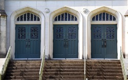 Mercy Hill Church, in Memphis, Tennessee, has three double doors on front of church.  Historic church is built of stone with green wooden doors.