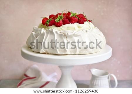 Meringue cake 'Pavlova' with fresh ripe raspberry and whipped cream on a light slate, stone or concrete background. Stock photo ©